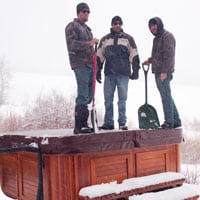 Men standing on the top of a covered hot tub